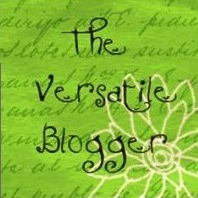 On a green background with faint writing and a white outline of a flower, the words 'The Versatile Blogger'.