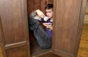 David Tennant, sitting in a wardrobe with a tea cup and saucer
