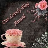 Text says 'One Lovely Blog Award'. There's also a pink rose and a pink and white teacup