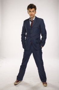 The Doctor in his blue suit, hands in pockets and eyebrows raised.