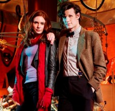 The Doctor and Amy in the Tardis. He, in his customary tweed jacket and bowtie, has his right arm on her left shoulder, she's wearing a red scarf and blue top with a jacket.