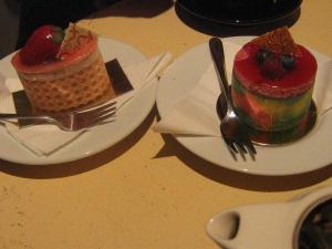 On plates with forks, a oval-shaped strawberry cake and a rainbow-coloured cake.