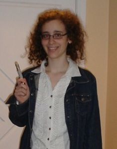 Chally in a white buttoned shirt and denim jacket, smiling and holding a sonic screwdriver.