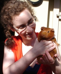 Chally, wearing a blue dress with an orange top over it, pale and bespectacled, with a curly plait hanging over the front of her shoulder, is holding Pepper upright. The sun is shinging on little ginger Pepper's nose, and she looks reasonably content.