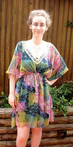 Me, a pale woman with glasses, standing in an outdoor setting. My curly hair is tied back. My left hand is on my hip with my right hand hanging down. My right knee is bent a little forward. There is a small smile on my face. I am looking directly at the camera. I am wearing a dress covered in dark blue, light blue, pink, yellow, and green splotches. The v-neck collar is bordered in sequins.