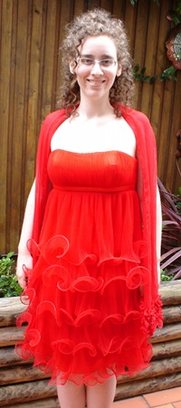 Me, a pale, curly haired woman with glasses, smiling in an outdoor setting. I am wearing a red scarf over a formal red dress. The dress is about knee-length, and has several layers of frills formed by plastic piping through the bottom of semi-sheer layers of the dress.
