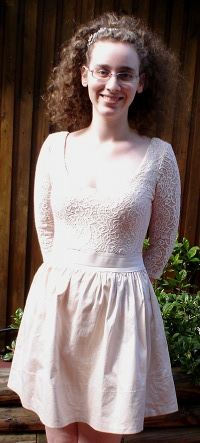 Me, a pale woman with curly hair and glasses, smiling. I am in an outdoor setting and have my hands behind my back. I am wearing a dress with a skirt that flares out to just above my knees. The top section is lacy.