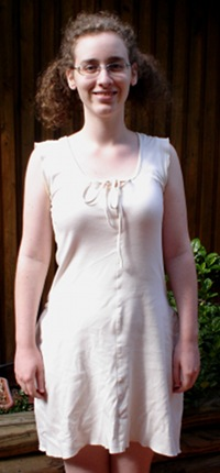 Me, a pale woman with curly hair and glasses, smiling. I am in an outdoor setting and have my hands at my sides. I am wearing a short cream dress.
