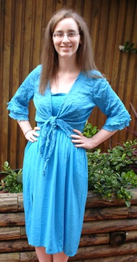 Me, a pale woman with glasses and temporarily straightened hair, stand in an outdoor setting with my hands on my hips. I am wearing a blue cropped cardigan over a blue knee-length dress.