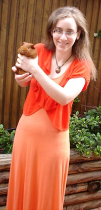 Me, a pale woman with glasses and temporarily straightened hair, stand in an outdoor setting holding a small orange guinea pig. I am wearing a long orange dress with a darker orange cropped cardigan as well as an orange and green necklace.