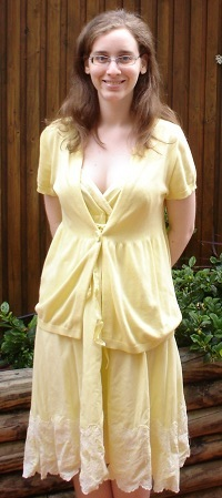 Me, a pale woman with glasses and temporarily straightened hair, in an outdoor setting. I have my hands behind my back. I am wearing a yellow short-sleeved cardigan over a yellow dress of knee length.