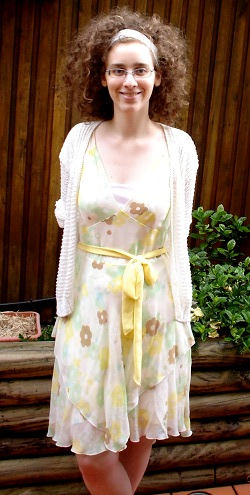 Me, a pale woman with glasses, standing in an outdoor setting. My curly hair is held back by a ribbon going vertically around the backs of my ears. I have my hands behind my back and am smiling. I am looking directly at the camera. I am wearing a cream coloured knee-length dress covered in green, brown and yellow flowers. There is a yellow tie around the waist, secured with an off-centre bow. I am wearing a white cardigan with it.