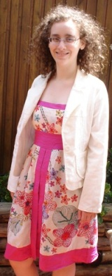 Me, a pale woman with curly hair and glasses, in an outdoor setting, smiling, with my hands behind my back. I am wearing a white jacket over a dress with a floral pattern and pink bands around the waist, neck and hem, and two down the front.