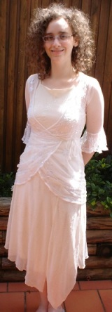 Me, a pale woman with curly hair and glasses, in an outdoor setting, smiling, with my hands behind my back. I am wearing an asymmetrical cream dress with sparkles, and a transparent white net top over it.