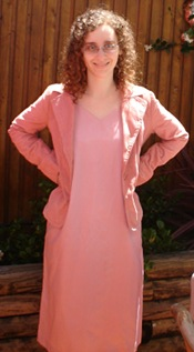 Me, a pale woman with curly hair and glasses, in an outdoor setting, with my hands on my hips. I am wearing a long pink dress with a corduroy jacket, also pink.