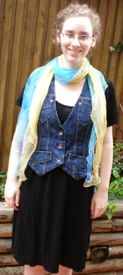 Me, a pale woman with curly hair and glasses, in an outdoor setting, with my hands by my sides. I am wearing a black knee-length dress with short sleeves with a denim waistcoast and a yellow and blue transparent scarf.