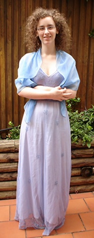 Me, a pale woman with curly hair and glasses, standing in an outdoor setting. My arms are folded across my chest and I am smiling. I am wearing a floor-length blue dress and a wrap in a different shade of blue.