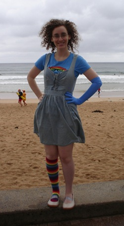 Me, a pale woman with curly hair and glasses, standing on a concrete ledge before a beach. I have my hands on my hips and am smiling. I am wearing a light blue denim dress and a blue t-shirt with an anthropomorphic rainbow on it. I have a long glove on my left arm and a rainbow knee-length sock on my right leg, with cream-coloured shoes. Surf lifesavers are behind me.