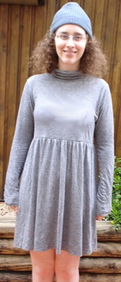 An outdoor setting. Me, a pale, curly haired woman with glasses, stand with my hands at my sides. I am wearing a grey turtleneck dress that ends before my knees and has long sleeves. I am wearing a grey beanie with it.
