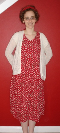 Me, a pale, curly haired woman with glasses, stand with my hands behind my back against a red wall, with white skirting and a bit of angled white ceiling visible. My hair is tied up with a red scarf. I am wearing a white cardigan over a long red dress with white daisies on it.