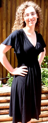 Me, a pale, curly haired woman with glasses, smiling in an outdoor setting. I have my hands on my hips and am wearing a black knee-length dress.