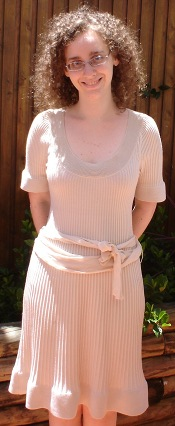 Me, a pale curly haired woman with glasses, in an outdoor setting, with my hands behind my back, and smiling. I am wearing a knee-length cream knit dress with a sash about the waist.