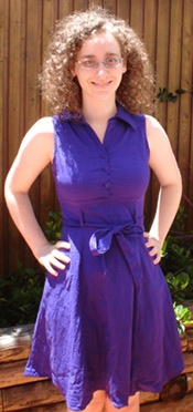 Me, a pale curly haired woman with glasses, in an outdoor setting, with my hands on my hips, and smiling. I am wearing a purple dress with a collar and a bow around the waist.