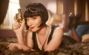 Phryne Fisher, with red lipstick and bobbed hair, is propped on her elbows, holding a gun.