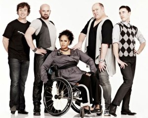 The cast of Outland, with Max, Andy, Fab, and Toby all standing around Rae.