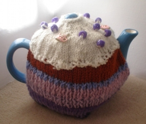A teacosy on a teapot. The teacosy looks like a cupcake and has purple and teapot-shaped beads on the icing.