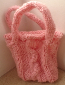 A small pink knitted bag with handles and a cable down the middle.