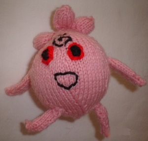 Igglybuff, a round, pink, smiling Pokemon with two arms, two legs, red eyes, a big smile, a swirl on its forehead, and three puffs of pink hair.